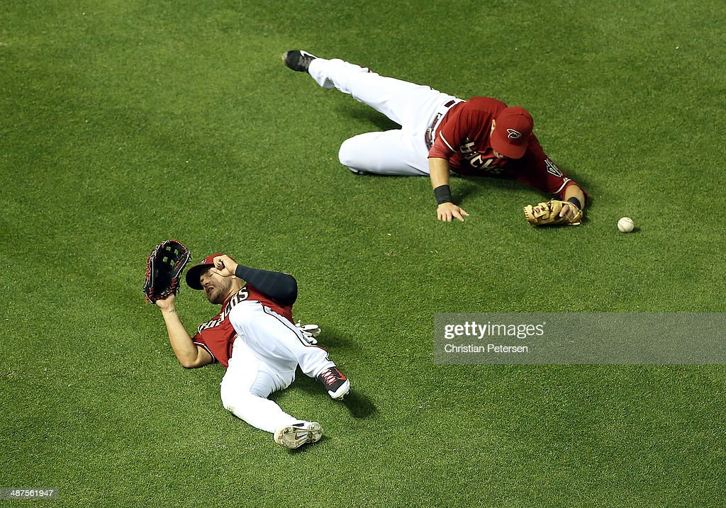 Outfielder Cody Ross #7 and infielder Cliff Pennington #4 of the Arizona Diamondbacks fall to the grass after being unable to catch a single during the 10th inning of the MLB game at Chase Field on April 30, 2014 in Phoenix, Arizona. The Diamodbacks defeated the Rockies 5-4 in 10 innings.