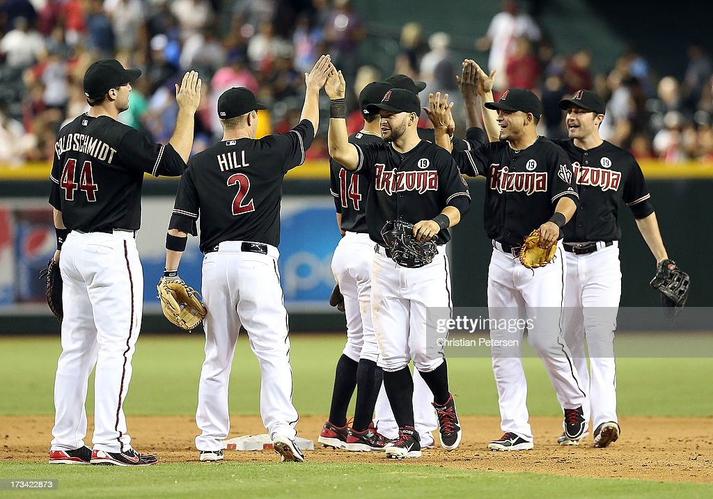 Outfielder <a gi-track='captionPersonalityLinkClicked' href=/galleries/search?phrase=Cody+Ross&family=editorial&specificpeople=545810 ng-click='$event.stopPropagation()'>Cody Ross</a> #7 of the Arizona Diamondbacks high-fives teammates after defeating the Milwaukee Brewers in the MLB game at Chase Field on July 13, 2013 in Phoenix, Arizona. The Diamondbacks defeated the Brewers 5-4.