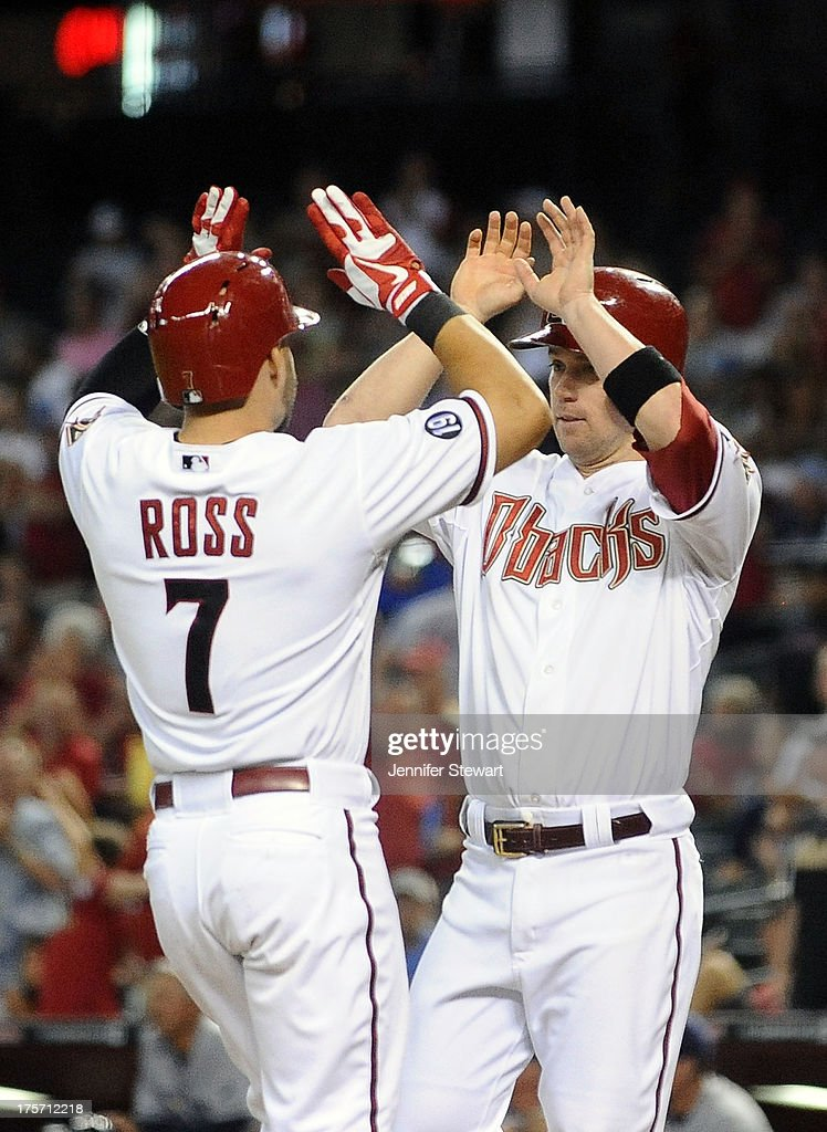 Outfielder Cody Ross #7 of the Arizona Diamondbacks is congratulated at home plate by teammate Aaron Hill #2 after hitting a three run home run against the Tampa Bay Rays in the fourth inning at Chase Field on August 6, 2013 in Phoenix, Arizona. The Diamondbacks defeated the Rays 6-1.