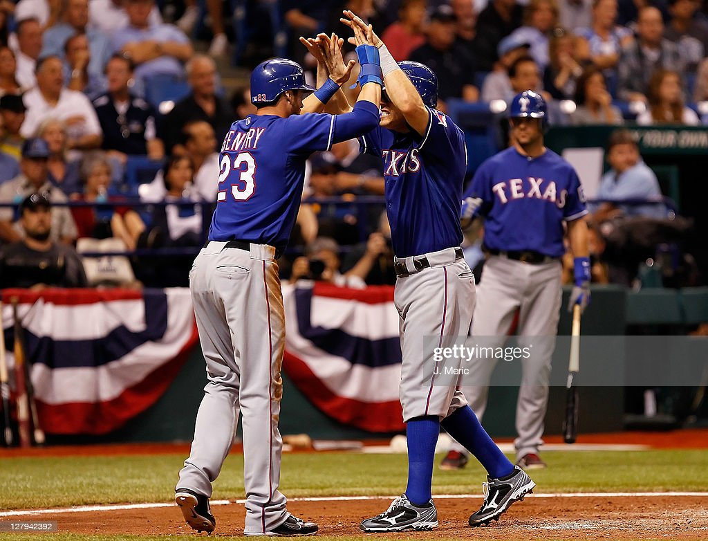 Outfielder Craig Gentry of the Texas Rangers congratules Ian Kinsler after he scored against the Tampa Bay Rays during Game Three of the American...