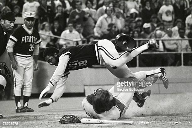 Outfielder Dave Parker of the Pittsburgh Pirates crashes into catcher Steve Yeager of the Los Angeles Dodgers in a collision at home plate during a...