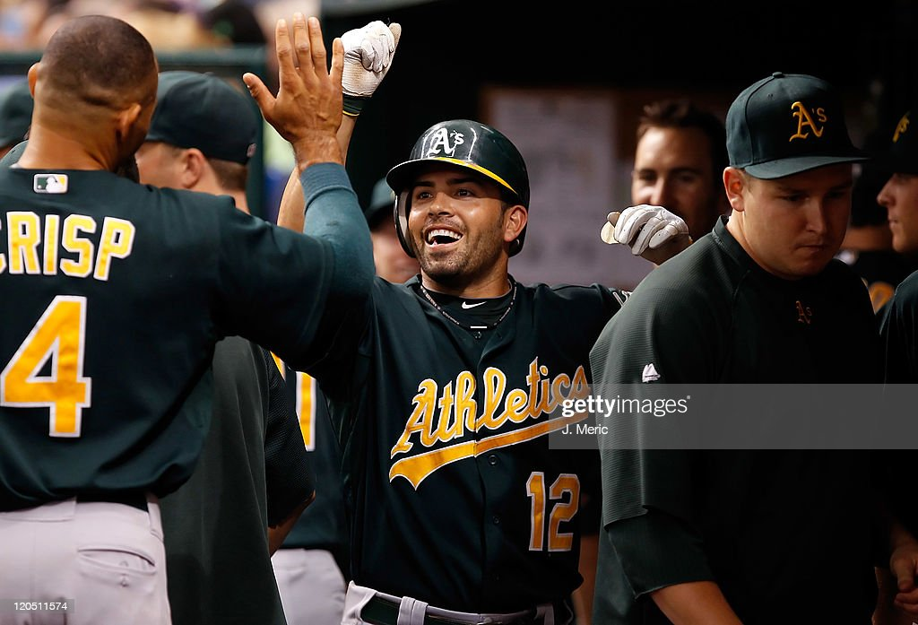 Outfielder <a gi-track='captionPersonalityLinkClicked' href=/galleries/search?phrase=David+DeJesus&family=editorial&specificpeople=206765 ng-click='$event.stopPropagation()'>David DeJesus</a> #12 of the Oakland Athletics is congratulated by <a gi-track='captionPersonalityLinkClicked' href=/galleries/search?phrase=Coco+Crisp&family=editorial&specificpeople=206376 ng-click='$event.stopPropagation()'>Coco Crisp</a> #4 after his home run against the Tampa Bay Rays during the game at Tropicana Field on August 6, 2011 in St. Petersburg, Florida.