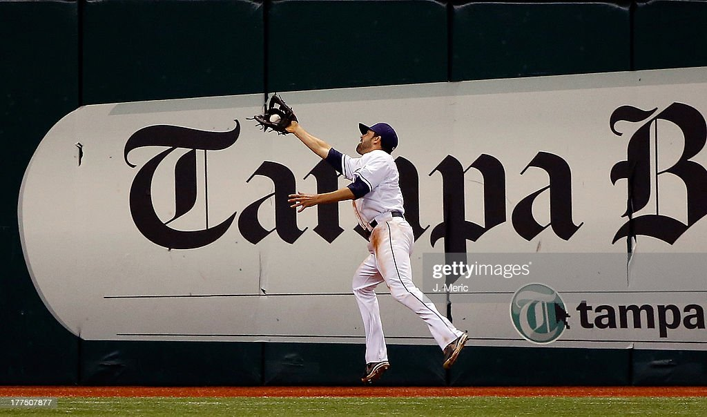 Outfielder <a gi-track='captionPersonalityLinkClicked' href=/galleries/search?phrase=David+DeJesus&family=editorial&specificpeople=206765 ng-click='$event.stopPropagation()'>David DeJesus</a> #7 of the Tampa Bay Rays catches a fly ball on the run against the New York Yankees during the game at Tropicana Field on August 23, 2013 in St. Petersburg, Florida.