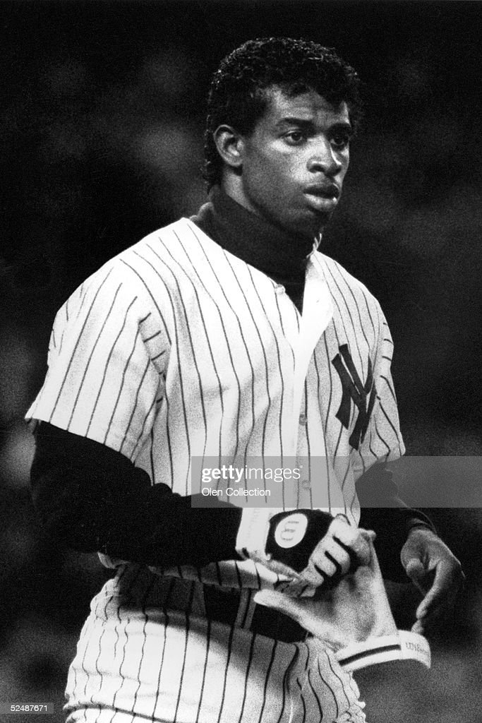 Outfielder Deion Sanders of the New York Yankees awaits his hat and glove after an at bat during a game on May 21 1990 against the Chicago White Sox...