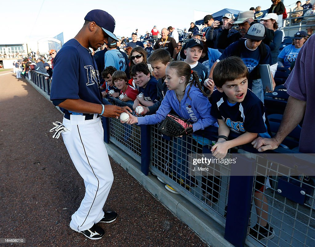 Outfielder <a gi-track='captionPersonalityLinkClicked' href=/galleries/search?phrase=Desmond+Jennings&family=editorial&specificpeople=5974085 ng-click='$event.stopPropagation()'>Desmond Jennings</a> #8 of the Tampa Bay Rays signs some autographs just prior to the start of the Grapefruit League Spring Training Game against the Pittsburgh Pirates at the Charlotte Sports Complex on March 25, 2013 in Port Charlotte, Florida.