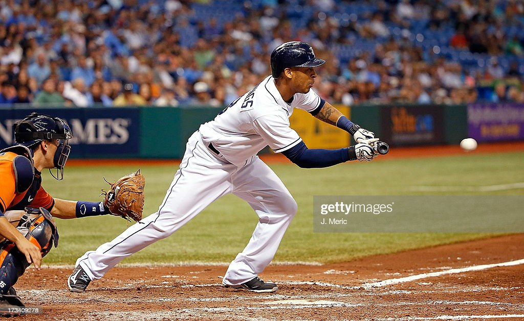 Outfielder <a gi-track='captionPersonalityLinkClicked' href=/galleries/search?phrase=Desmond+Jennings&family=editorial&specificpeople=5974085 ng-click='$event.stopPropagation()'>Desmond Jennings</a> #8 of the Tampa Bay Rays squeezes home the tying run in the fifth inning against the Houston Astros during the game at Tropicana Field on July 13, 2013 in St. Petersburg, Florida.