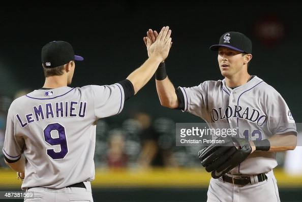 Outfielder Drew Stubbs of the Colorado Rockies highfives DJ LeMahieu after defeating the Arizona Diamondbacks in the MLB game at Chase Field on April...