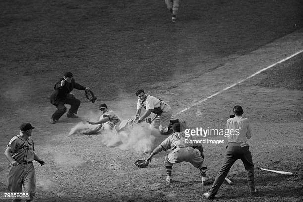 Outfielder Enos Slaughter of the St Louis Cardinals is tagged out at the plate by catcher Dick West of the Cincinnati Reds in the eleventh inning of...