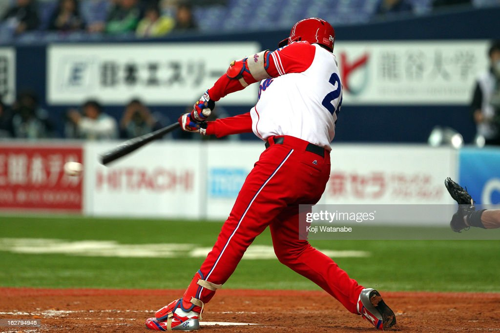 Outfielder Frederich Cepeda #24 of Cuba hits an RBI single in the top half of the fifth inning during the friendly game between Hanshin Tigers and Cuba at Kyocera Dome Osaka on February 27, 2013 in Osaka, Japan.
