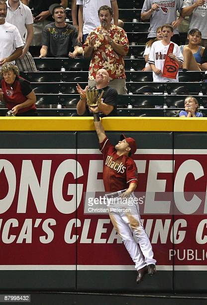 Outfielder Gerardo Parra of the Arizona Diamondbacks attempts to catch a solo home run hit by Chris Burke of the San Diego Padres during the major...
