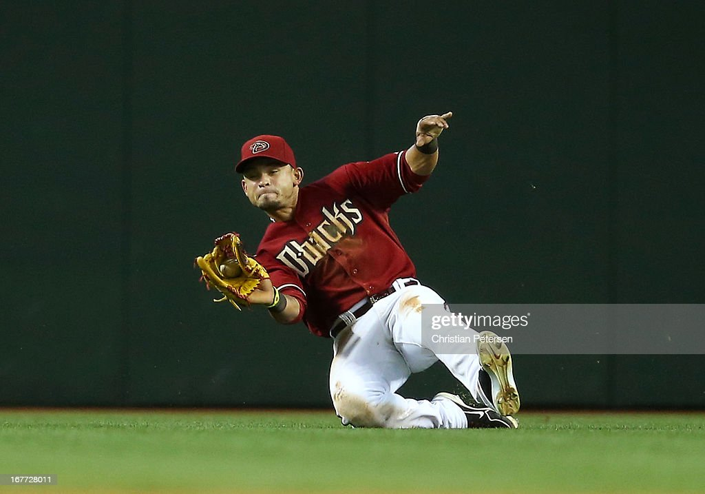 Outfielder <a gi-track='captionPersonalityLinkClicked' href=/galleries/search?phrase=Gerardo+Parra&family=editorial&specificpeople=4959447 ng-click='$event.stopPropagation()'>Gerardo Parra</a> #8 of the Arizona Diamondbacks makes a sliding catch on a fly ball hit by Nolan Arenado (not pictured) of the Colorado Rockies during the seventh inning of the MLB game at Chase Field on April 28, 2013 in Phoenix, Arizona.
