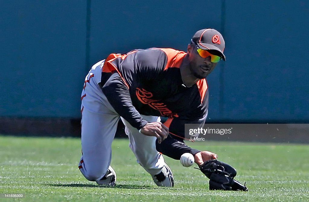 Outfielder Jai Miller of the Baltimore Orioles cannot come up with this catch against the Atlanta Braves during a Grapefruit League Spring Training...