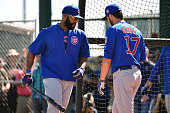 Outfielder Jason Heyward of the Chicago Cubs walks by teammate Kris Bryant during batting practice at a spring training workout at Sloan Park on...