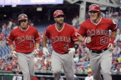 Outfielder JB Schuck firstbaseman Albert Pujols and outfielder Mike Trout of the Los Angeles Angels jog towards the dugout after Pujols hit a...
