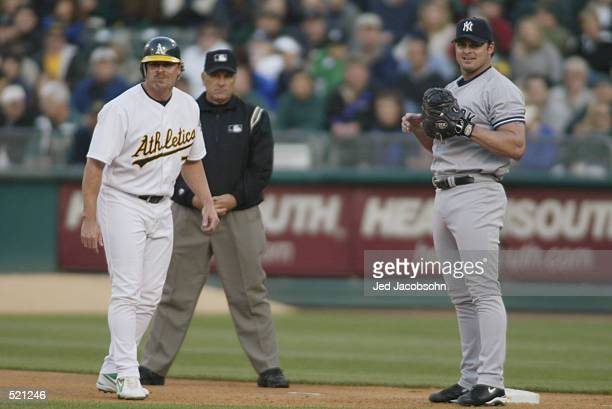 Outfielder Jeremy Giambi of the Oakland A's leads off of first base as Jason Giambi of the New York Yankees waits on the base for a throw during the...
