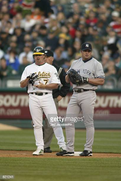 Outfielder Jeremy Giambi of the Oakland A's stands on first base with Jason Giambi of the New York Yankees during the game at Network Associates...