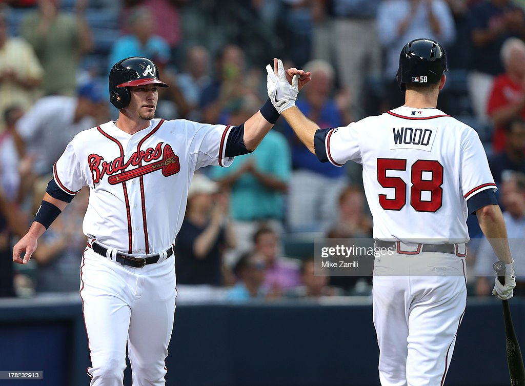Outfielder Joey Terdoslavich #25 of the Atlanta Braves is congratulated by teammate and pitcher Alex Wood #58 after Terdoslavich scored a run in the second inning during the game against the Cleveland Indians at Turner Field on August 27, 2013 in Atlanta, Georgia.