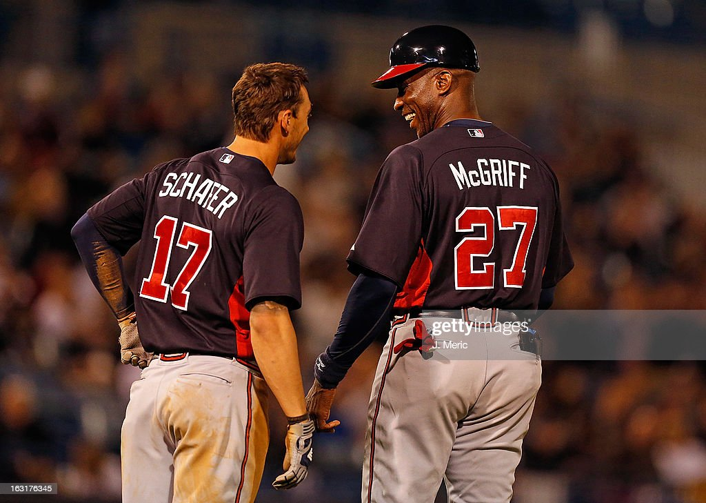Outfielder Jordan Schafer #17 of the Atlanta Braves shares a laugh with instructor Fred McGriff #27 inbetween innings against the New York Yankees during a Grapefruit League Spring Training Game at George M. Steinbrenner Field on March 5, 2013 in Tampa, Florida.