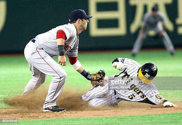 Outfielder Keiichi Hirano of Hanshin Tigers steals second base as he slides in as Infielder Dustin Pedroia of Boston Red Sox fails to tag out during...