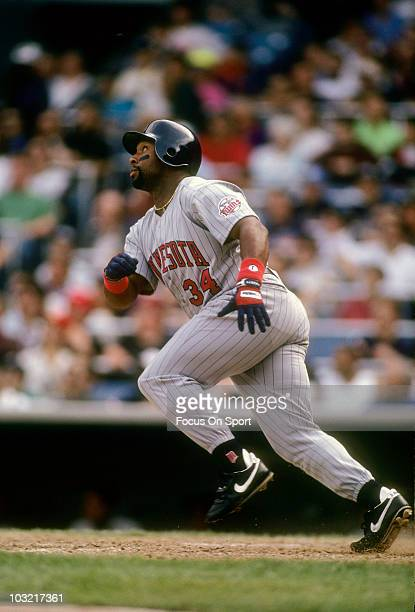 Outfielder Kirby Puckett of the Minnesota Twins races out of the batters box watching the flight of his ball against the New York Yankees circa 1993...