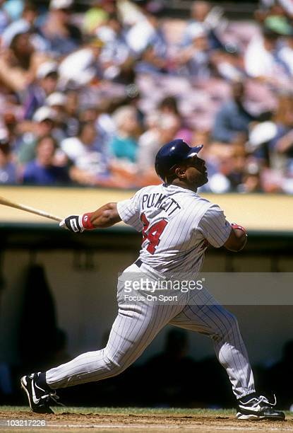 Outfielder Kirby Puckett of the Minnesota Twins swings and watches the flight of his ball against the Oakland Athletics circa 1995 during a MLB...