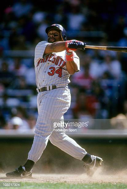 Outfielder Kirby Puckett of the Minnesota Twins swings and watches the flight of his ball against the New York Yankees circa 1993 during a MLB...