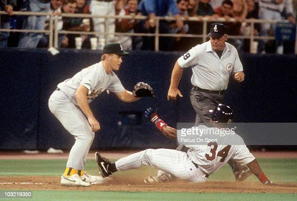 Outfielder Kirby Puckett of the Minnesota Twins swings slides into 3rd base safe against the Oakland Athletics circa 1993 during a MLB baseball game...