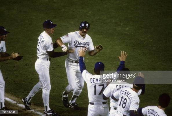 Outfielder Kirk Gibson of the Los Angeles Dodgers rounds third base and is greeted by teammates after he hit a pitch hit homerun in the bottom of the...