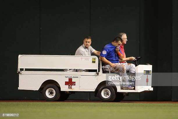 Outfielder Kyle Schwarber of the Chicago Cubs is taken off the field on a cart after an injury during the second inning of the MLB game against the...