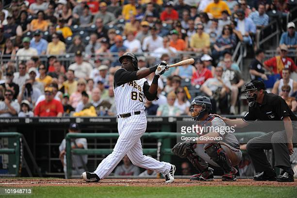 Outfielder Lastings Milledge of the Pittsburgh Pirates bats as catcher Dave Ross of the Atlanta Braves and umpire Tim Timmons look on during a game...