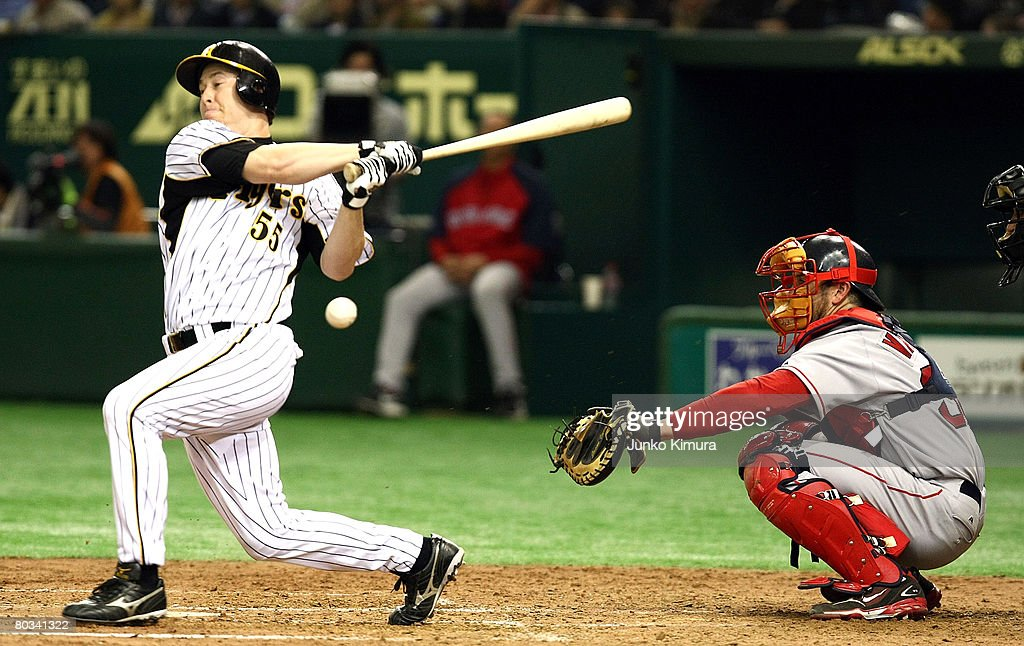 Outfielder Lew Ford #55 of Hanshin Tigers misses to hit the ball as Catcher Jason Varitek #33 of Boston Red Sox waits for the ball pitches during preseason friendly between Boston Red Sox and Hanshin Tigers at Tokyo Dome on March 22, 2008 in Tokyo, Japan.