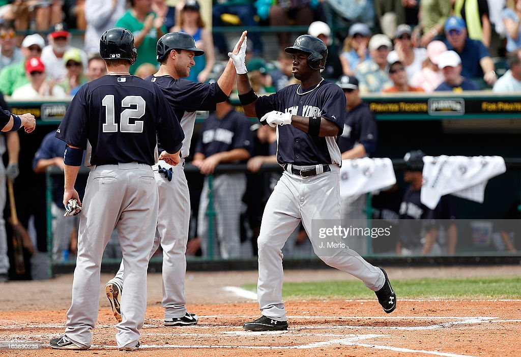 Outfielder Melky Mesa #63 of the New York Yankees is congratulated after his grand slam against the Pittsburgh Pirates during a Grapefruit League Spring Training Game at McKechnie Field on March 17, 2013 in Bradenton, Florida.