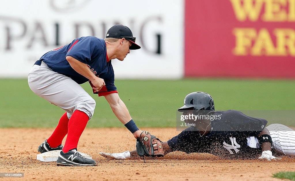 Outfielder Melky Mesa #63 of the New York Yankees is out at second as infielder Brock Holt #26 of the Boston Red Sox applies the tag during a Grapefruit League Spring Training Game at George M. Steinbrenner Field on March 20, 2013 in Tampa, Florida.