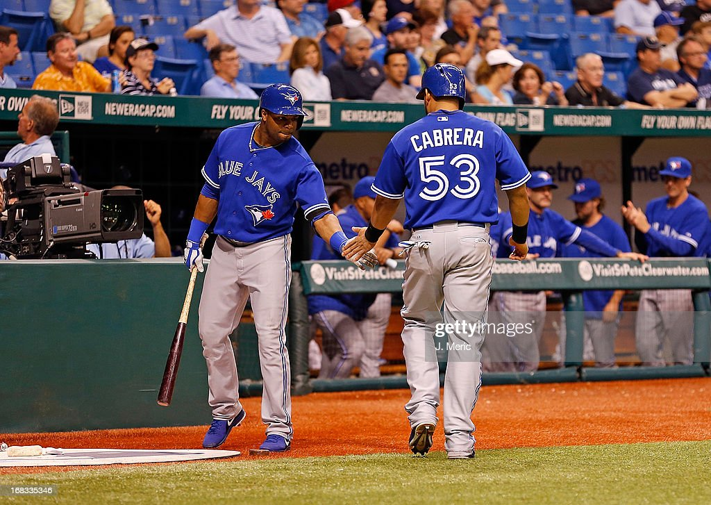 Outfielder Rajai Davis #11 of the Toronto Blue Jays congratulates Melky Cabrera #53 after scoring against the Tampa Bay Rays during the game at Tropicana Field on May 8, 2013 in St. Petersburg, Florida.