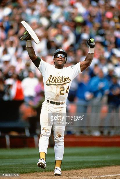 Outfielder Rickey Henderson of the Oakland Athletics celebrates after stealing third base against the New York Yankees during a Major League Baseball...
