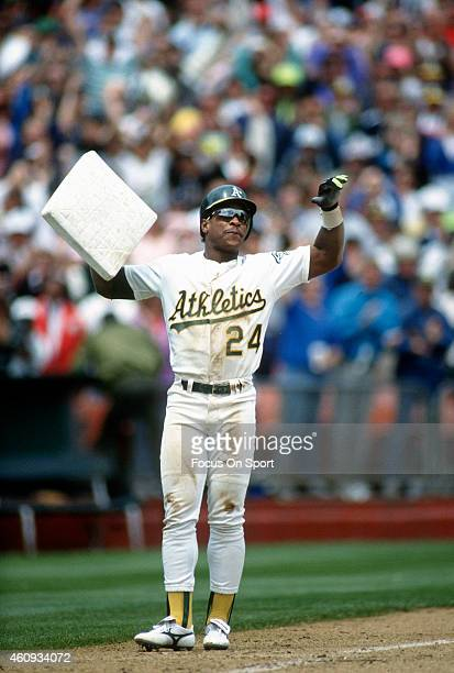 Outfielder Rickey Henderson of the Oakland Athletics holding up third base after stealing it against the New York Yankees during a Major League...