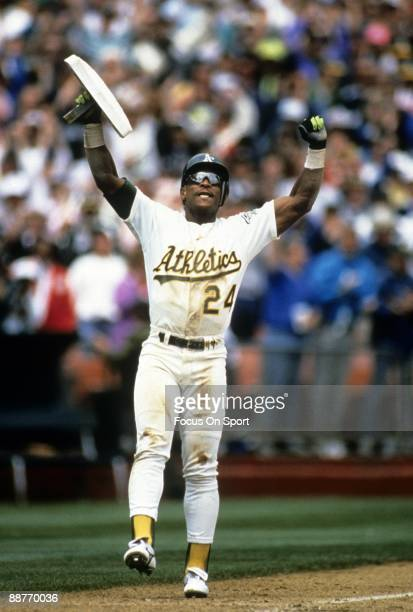 Outfielder Rickey Henderson of the Oakland Athletics holds up the third base bag after stealing it against the New York Yankees given him 939 career...