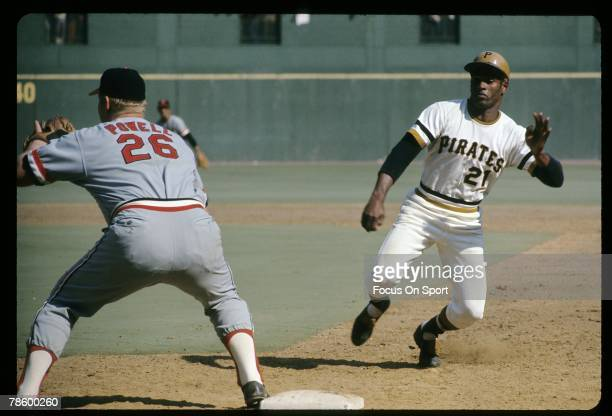 Outfielder Roberto Clemente of the Pittsburgh Pitrates slides back into first base as Baltimore Orioles first baseman Boog Powell waits on the throw...