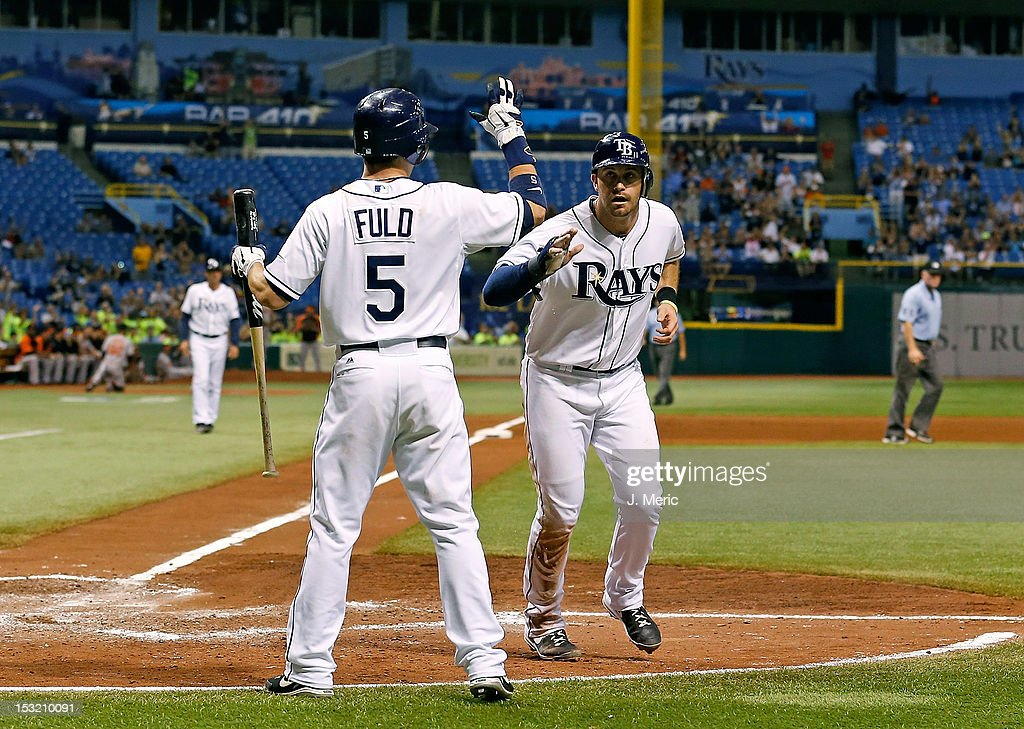 Outfielder <a gi-track='captionPersonalityLinkClicked' href=/galleries/search?phrase=Sam+Fuld&family=editorial&specificpeople=4505687 ng-click='$event.stopPropagation()'>Sam Fuld</a> #5 of the Tampa Bay Rays congratulates <a gi-track='captionPersonalityLinkClicked' href=/galleries/search?phrase=Evan+Longoria&family=editorial&specificpeople=2349329 ng-click='$event.stopPropagation()'>Evan Longoria</a> #3 after he scored on a sacrifice against the Baltimore Orioles during the game at Tropicana Field on October 1, 2012 in St. Petersburg, Florida.