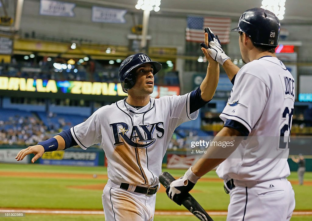 Outfielder <a gi-track='captionPersonalityLinkClicked' href=/galleries/search?phrase=Sam+Fuld&family=editorial&specificpeople=4505687 ng-click='$event.stopPropagation()'>Sam Fuld</a> #5 of the Tampa Bay Rays is congratulated by Matt Joyce #20 after scoring against the New York Yankees during the game at Tropicana Field on September 5, 2012 in St. Petersburg, Florida.