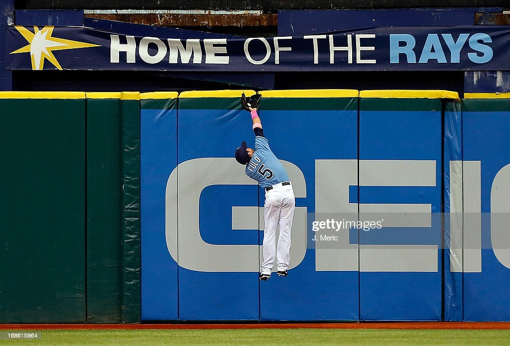 Outfielder <a gi-track='captionPersonalityLinkClicked' href=/galleries/search?phrase=Sam+Fuld&family=editorial&specificpeople=4505687 ng-click='$event.stopPropagation()'>Sam Fuld</a> #5 of the Tampa Bay Rays makes a catch at the top of the wall against the San Diego Padres during the game at Tropicana Field on May 12, 2013 in St. Petersburg, Florida.