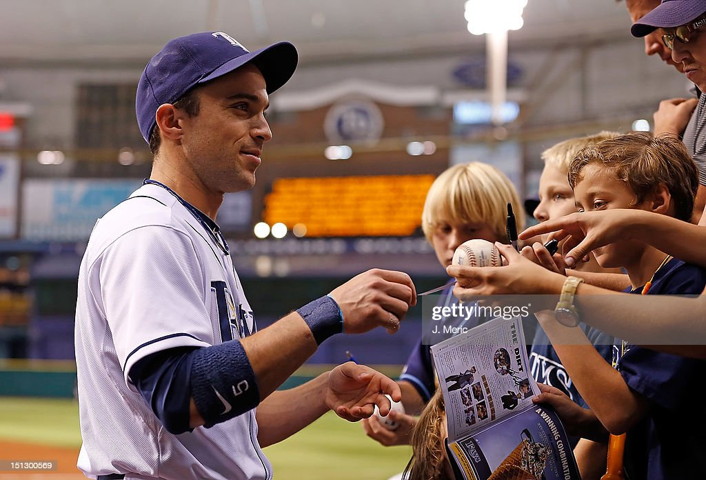 Outfielder Sam Fuld #5 of the Tampa Bay Rays signs some autographs just prior to the start of the game against the New York Yankees at Tropicana Field on September 5, 2012 in St. Petersburg, Florida.