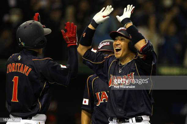 Outfielder Seiichi Uchikawa of Japan celebrates after scoring hits a three run home run in the bottom half of the second inning during the World...