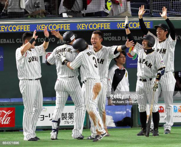 Outfielder Seiichi Uchikawa of Japan is congratulated by his team mates after hitting a sacrifice fly to make it 56 in the bottom of the eighth...