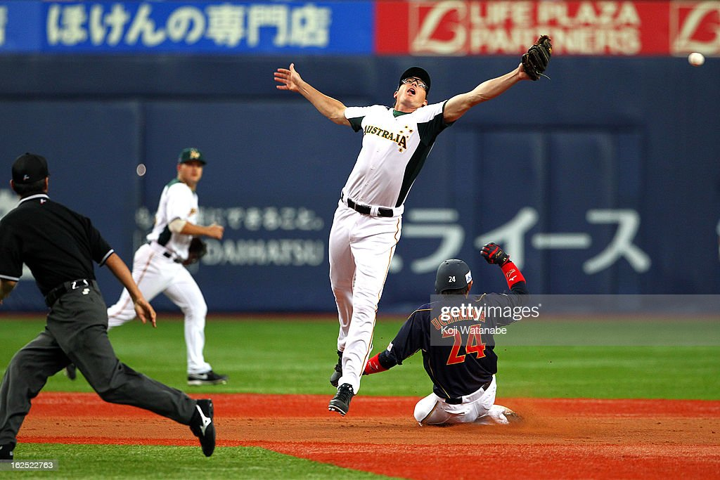 Outfielder Seiichi Uchikawa #24 of Japan steals a base in the top half of the first inning during the international friendly game between Australia and Japan at Kyocera Dome Osaka on February 24, 2013 in Osaka, Japan.