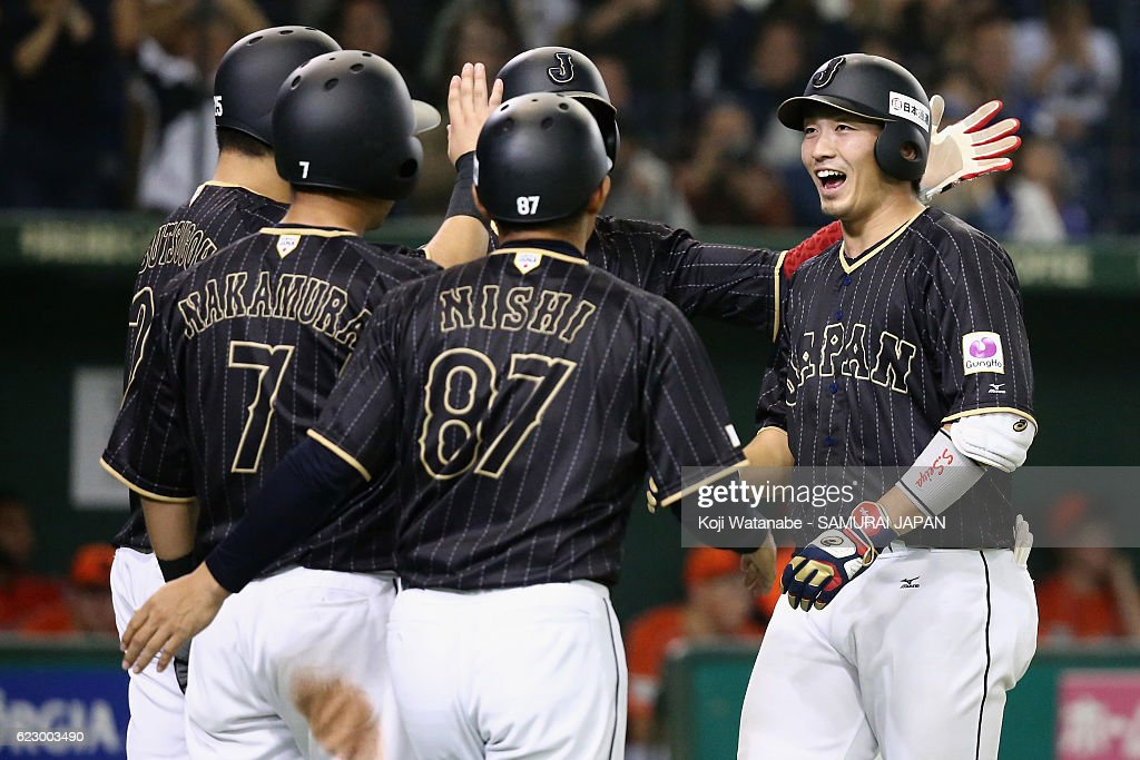 Outfielder Seiya Suzuki (1st R) #51 of Japan celebrates with his team mates after hitting a grand slam in the tenth inning during the international friendly match between Netherlands and Japan at the Tokyo Dome on November 13, 2016 in Tokyo, Japan.