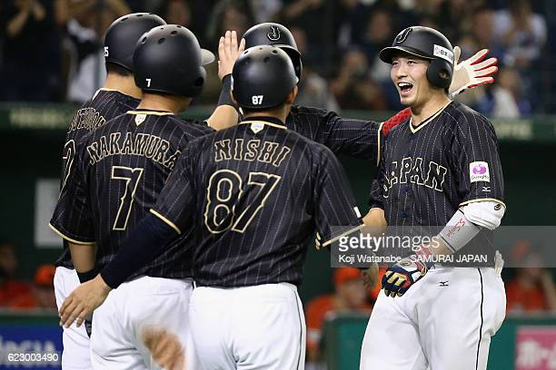 Outfielder Seiya Suzuki of Japan celebrates with his team mates after hitting a grand slam in the tenth inning during the international friendly...