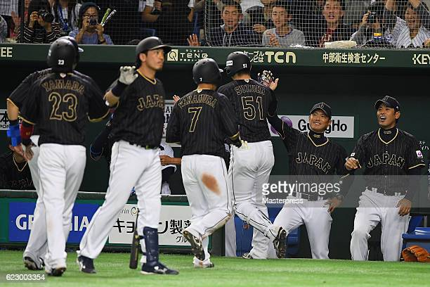 Outfielder Seiya Suzuki of Japan is congratulated by Head coach Hiroki Kokubo of Japan after hitting a grand slam in the tenth inning during the...