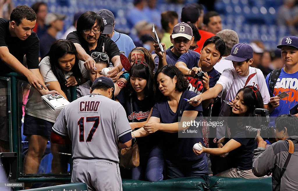 Outfielder <a gi-track='captionPersonalityLinkClicked' href=/galleries/search?phrase=Shin-Soo+Choo&family=editorial&specificpeople=196543 ng-click='$event.stopPropagation()'>Shin-Soo Choo</a> #17 of the Cleveland Indians signs some autographs just prior to the start of the game against the Tampa Bay Rays at Tropicana Field on July 18, 2012 in St. Petersburg, Florida.