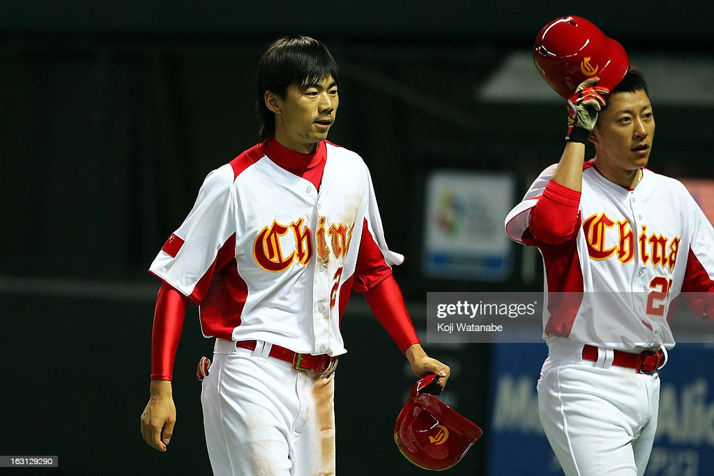 Outfielder Xiao Cui #27 (L) of China celebrates after scoring during the World Baseball Classic First Round Group A game between China and Brazil at Fukuoka Yahoo! Japan Dome on March 5, 2013 in Fukuoka, Japan.